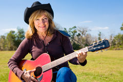 Country Western Musician. Beautiful mature woman plays country western music on her guitar stock image