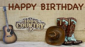 Country and western objects on a wood background. Cowboy boots hat and guitar standing on a wood background with happy birthday in brown text with a 100% country stock photo