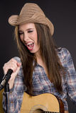 Country western singer playing guitar singing song. Attractive female country and western singer with guitar and microphone stock photo