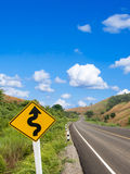 Country winding road sign with blue sky Royalty Free Stock Photos