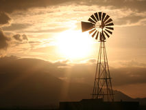 Country Windmill. Windmill in the country with mountains and a sunset Royalty Free Stock Photo