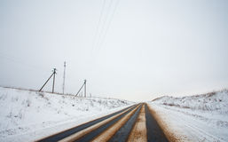 Country winter road and power line Stock Photography