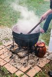 A country woman preparing a Romanian traditional food at the cauldron. Close view royalty free stock photography