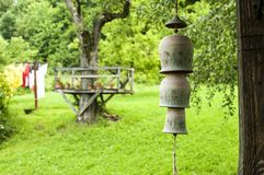 Countryhouse garden view with clay wind bells. Countryhouse garden view with ceramic clay pottery decorative garden wind chime bells on a rope in front Stock Image
