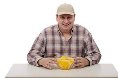 A countryman shows juicy yellow watermelon. A countryman in a plaid shirt shows juicy yellow watermelon Royalty Free Stock Images