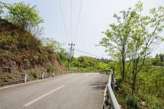 Countryroad d'asphalte de Hillside en ressort ensoleillé Image stock