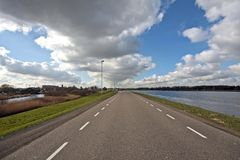 Countryroad in the Netherlands. Countryroad along a river in the Netherlands Royalty Free Stock Images
