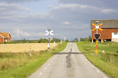 Countryroad with old railroad crossing royalty free stock image