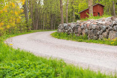 Countryroad with a stonewall, Sweden. Side of a countryroad with a stonewall and a red house in Sweden during summer Royalty Free Stock Photography
