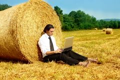 Countryside. A business man in a countryside with a laptop Royalty Free Stock Image