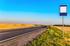 Countryside asphalt road with markings and empty information road sign Stock Images