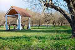 Countryside backyard with family gazebo in sunny day. Spring has come. Outdoor wooden gazebo for family dinners on a green vernal lawn of a country house yard Stock Images