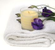 Countryside Bathroom. Wild purple flowers and relaxing aromatherapy scented candle on white bath towel for a calming spa and bathroom Royalty Free Stock Photos