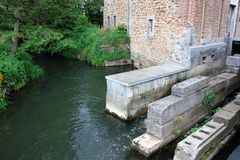 Haven of water, leaves and stone. Countryside in Belgium, little home made of bricks, river and bushes royalty free stock image