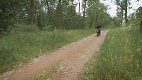 The countryside. bike rides along the dirt path among the trees and bushes. stock footage