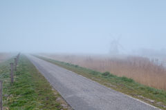 Countryside bike road and windmill in fog Royalty Free Stock Images