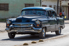 In the countryside black american vintage car drives on the street Stock Photography