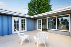 Countryside blue house with concrete floor patio area with chairs. Royalty Free Stock Photo