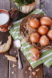 Countryside breakfast with eggs. Brown chicken eggs in straw basket served for breakfast with ceramic cup of milk, silver spoon and bread pieces on rustic wooden royalty free stock photo
