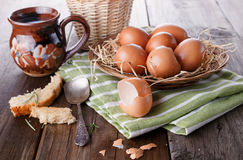 Countryside breakfast with eggs. Brown chicken eggs in straw basket served for breakfast with ceramic cup of milk, silver spoon and bread pieces on rustic wooden royalty free stock photography