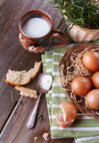 Countryside breakfast with eggs. Brown chicken eggs in straw basket served for breakfast with ceramic cup of milk, silver spoon and bread pieces on rustic wooden stock photo
