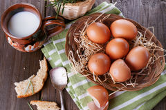 Countryside breakfast with eggs. Brown chicken eggs in straw basket served for breakfast with ceramic cup of milk, silver spoon and bread pieces on rustic wooden stock image