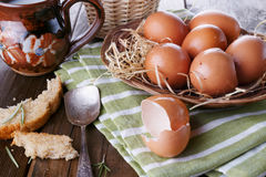 Countryside breakfast with eggs. Brown chicken eggs in straw basket served for breakfast with ceramic cup of milk, silver spoon and bread pieces on rustic wooden royalty free stock photos
