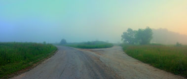 Countryside crossroads. Countryside road, foggy summer morning Royalty Free Stock Images