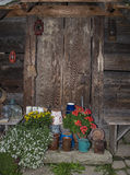 Countryside. Entrance to a very old hut from 19th century with some clay pots and flowers in the foreground Royalty Free Stock Photos