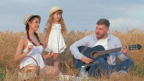 Countryside family leisure, young man plays guitar while his beautiful wife and little daughter dance laughing at picnic stock footage