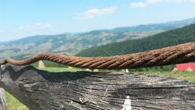 Countryside fence. Detail of a countryside wooden fence with hills in the background royalty free stock images