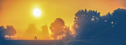 Countryside foggy scenic nature landscape. Of a countryside view with a windmill stock images