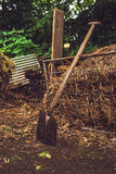 Countryside Garden with Shovel and Hay. Trees in Background. Royalty Free Stock Photo