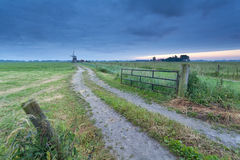 Countryside ground road to windmill Stock Photography