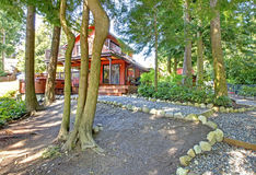 Countryside house backyard with gravel walkway. Red countryside house with walkout deck and jacuzzi. View of trees and gravel walkway Stock Photos