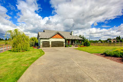 Countryside house exterior with garage and driveway Royalty Free Stock Image