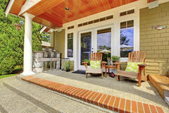 Countryside house exterior. View of column porch with chairs and concrete floor. Royalty Free Stock Photos