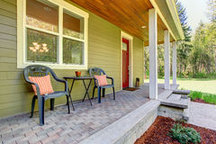 Countryside house exterior. View of entrance porch with chairs Royalty Free Stock Images