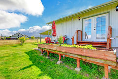 Countryside house exterior with walkout deck and small patio are. Countryside house exterior with small patio area. Table with chairs, umbrella and barbecue stock photos