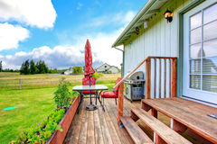 Countryside house exterior with walkout deck and small patio are Stock Image