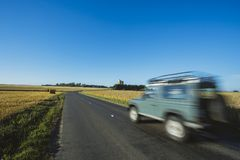 Countryside landscape and agricultural fields in summer. Country road and straw bales after harvesting on a sunny day in. Yellow wheat field with straw bales Royalty Free Stock Images
