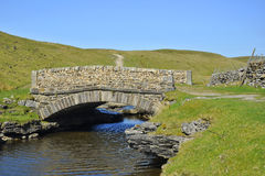 Countryside landscape: bridge, river, blue sky. English countryside landscape: small stone bridge over river stream between grassy fields on hill slopes, taken Stock Images