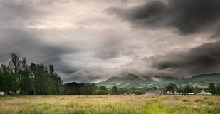 Countryside landscape image across to mountains. Beautiful landscape across countryside to mountains in distance with moody sky Stock Photo