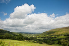 Countryside landscape image Summer valley. Beautiful landscape across countryside to mountains in distance with moody sky Royalty Free Stock Photo
