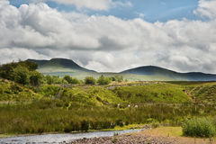 Countryside landscape image to mountains. Beautiful landscape across countryside to mountains in distance with moody sky Royalty Free Stock Photos