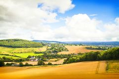 Countryside landscape with meadow and sky. Hay bales or straw on agricultural fields Royalty Free Stock Photography