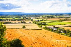Countryside landscape with meadow and sky. Hay bales or straw on agricultural fields Stock Photography