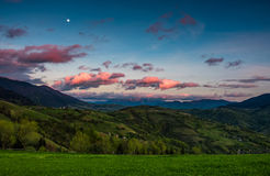 Countryside landscape in mountains at dusk and moonrise. Countryside landscape in mountains at dusk with moonrise. grassy meadow on a hillside behind the fence Royalty Free Stock Images