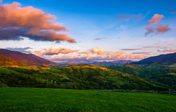 Countryside landscape in mountains at sunset. Grassy meadow on a hill behind the fence. spectacular evening sky with red clouds Royalty Free Stock Photo
