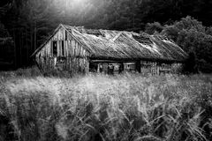 Countryside landscape of old barn near forest. Aged old barn in rural countryside, black and white stock photo